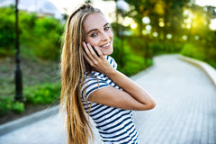 Portrait of a smiling beautiful woman talking on the phone Stock Photos