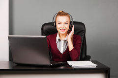 Portrait of smiling beautiful young call center operator in headset, at office Stock Photos