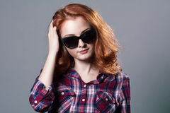 Portrait of a smiling beautiful young red-haired girl in sunglas Royalty Free Stock Photos
