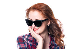 Portrait of a smiling beautiful young red-haired girl in sunglasses looking away royalty free stock image