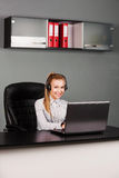 Portrait of smiling beautiful young support phone operator in headset, at office Stock Photos