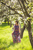 Portrait of smiling beautiful young woman enjoying warm sunny da. Y in spring blossoms of apple trees stock photo