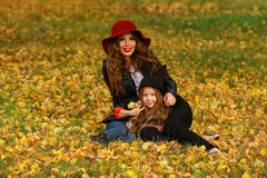 Portrait of smiling beautiful young woman and her little daughter sitting on grass autumn. Royalty Free Stock Photo