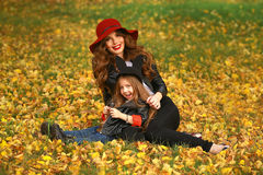 Portrait of smiling beautiful young woman and her little daughter sitting on grass autumn. Stock Images