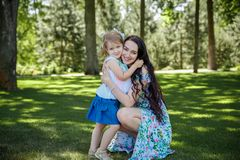 Portrait of smiling beautiful young woman and her little daughter sitting on grass stock photos