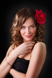 Portrait of smiling beautiful young woman  with Red flower. Glamour portrait of smiling beautiful young woman  with Red flower in brown long ringlets hair Stock Photography