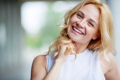 Portrait of smiling beautiful young woman touching her hair. Young woman touching her long blond hair, looking at camera Stock Images