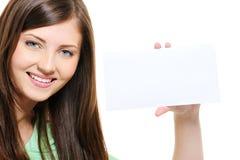 Portrait of smiling beauty girl holding white card. Close-up portrait of smiling young beauty girl holding white card Royalty Free Stock Photography