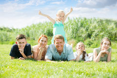 Portrait of smiling big family lying together on green lawn outd Royalty Free Stock Photo