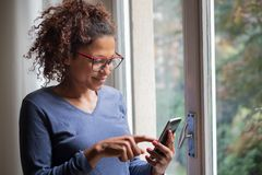 Happy black woman near window reading phone message. Portrait of smiling black woman standing beside window royalty free stock photography