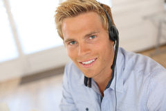 Portrait of smiling blond man talking on phone with headset Stock Photography