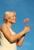 Portrait of smiling blonde with flower. Portrait of attractive woman with beautiful flower in hands relaxing  in country Stock Images