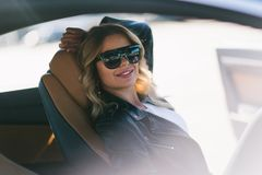 Portrait of smiling blonde with long hair behind wheel in car. royalty free stock images