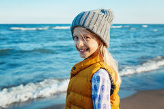 Portrait of smiling blonde white Caucasian child kid girl  with long hair, wearing yellow jacket gilet and grey hat Royalty Free Stock Photo