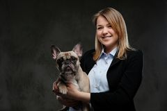 Portrait of a smiling blonde woman breeder holds her cute pug. Isolated on dark textured background. stock images
