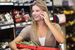 Portrait of smiling blonde woman buying vegetables and phoning Royalty Free Stock Image