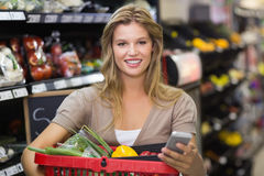 Portrait of smiling blonde woman buying vegetables and using her smartphone Stock Photo
