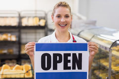 Portrait of a smiling blonde woman holding a sign Royalty Free Stock Photos