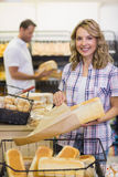 Portrait of a smiling blonde woman taking a bread on her paper bag Stock Images