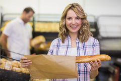 Portrait of a smiling blonde woman taking a bread Royalty Free Stock Photos