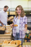Portrait of a smiling blonde woman taking a bread Stock Images