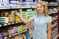 Portrait of smiling blonde woman taking a product in shelves Stock Image