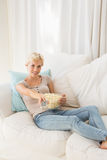 Portrait smiling blonde woman watching TV and eating pop corn Stock Image