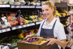 Portrait of a smiling blonde worker holding a box with vegetables Royalty Free Stock Photos