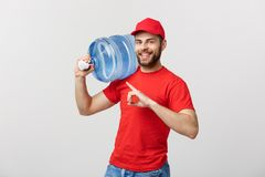 Portrait smiling bottled water delivery courier in red t-shirt and cap carrying tank of fresh drink and pointing finger. Isolated over white background Royalty Free Stock Photography