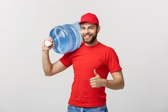 Portrait smiling bottled water delivery courier in red t-shirt and cap carrying tank of fresh drink and showing thumb up. Isolated over white background Royalty Free Stock Photography