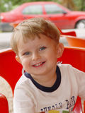 Portrait of the smiling boy. Portrait of the little boy sitting in the red chair Royalty Free Stock Photos