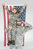 portrait of smiling boy with american flag sitting on fathers shoulder in military uniform stock photo