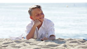 Portrait of smiling boy on beach. Portrait of smiling boy in elementary school age lying on beach on sunny weather stock video