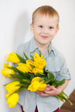 Portrait of Smiling boy with a bouquet of yellow tulips flowers in hands standing near white wall. Smiling boy holding a bouquet of yellow tulips isolated on Stock Images