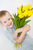 Portrait of Smiling boy with a bouquet of yellow tulips flowers in hands standing near white wall. Smiling boy holding a bouquet of yellow tulips isolated on Royalty Free Stock Photo