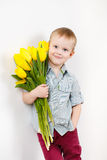 Portrait of Smiling boy with a bouquet of yellow tulips flowers in hands standing near white wall. Smiling boy holding a bouquet of yellow tulips isolated on Royalty Free Stock Photography