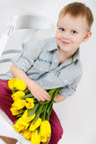 Portrait of Smiling boy with a bouquet of yellow tulips flowers in hands standing near white wall. Smiling boy holding a bouquet of yellow tulips isolated on Stock Image