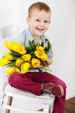 Portrait of Smiling boy with a bouquet of yellow tulips flowers in hands standing near white wall. Smiling boy holding a bouquet of yellow tulips isolated on Royalty Free Stock Photos