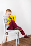 Portrait of Smiling boy with a bouquet of yellow tulips flowers in hands standing near white wall. Smiling boy holding a bouquet of yellow tulips isolated on Royalty Free Stock Images