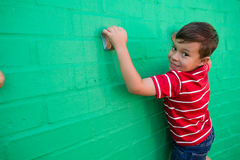 Portrait of smiling boy climbing wall at playground Royalty Free Stock Photos