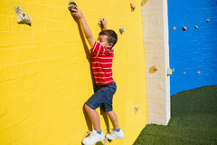Portrait of smiling boy climbing yellow wall at playground Royalty Free Stock Photos