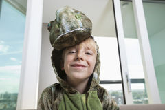Portrait of smiling boy in dinosaur costume at home Stock Image