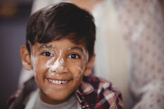 Portrait of smiling boy with flour on face Stock Photo