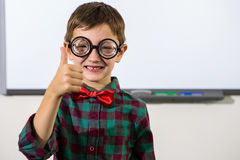 Portrait of smiling boy gesturing thumbs up sign. In classroom Stock Image