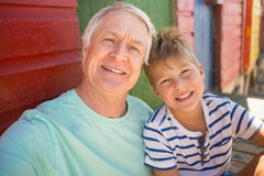 Portrait of smiling boy with grandfather sitting by wall. At beach Royalty Free Stock Photo