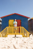 Portrait of smiling boy with grandfather standing at beach hut Royalty Free Stock Image