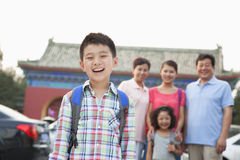 Portrait of smiling boy with his family in the background, outdoors Stock Image