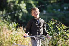 Portrait of smiling boy holding fishing net while standing in forest. On sunny day Stock Image