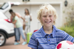 Portrait of smiling boy holding soccer ball in driveway Royalty Free Stock Image