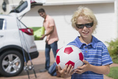 Portrait of smiling boy holding soccer ball in sunny driveway Stock Image